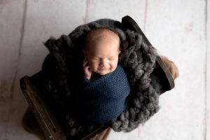 Newborn baby boy wrapped up posed in a bed