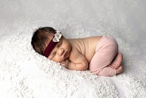 Baby girl posed on white lace backdrop in pink pants with headband- Newborn photography in Augusta georgia