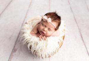 Newborn baby girl posed in wicker basket with pink bow headband- Martinez, Georgia